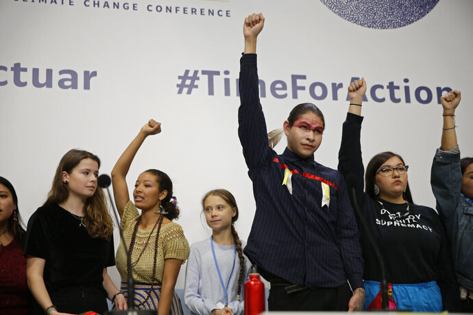 Climate activist Greta Thunberg, centre, stands with other young activists at the COP25 Climate summit in Madrid, Spain, Monday, Dec. 9, 2019. Thunberg is in Madrid where a global U.N. sponsored climate change conference is taking place. (AP Photo/Andrea Comas)