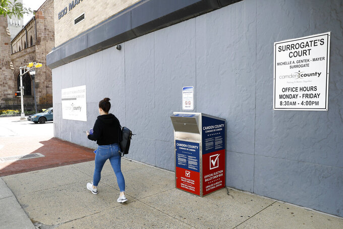FILE - In this July 1, 2020, file photo, a woman walks past a vote-by-mail drop box for the upcoming New Jersey primary election outside the Camden, N.J., Administration Building. Democrats plan to move quickly on one of the first bills of the new Congress, which would set federal election standards. The For the People Act would require states to offer early voting, same-day registration and the option of absentee voting for all registered voters. (AP Photo/Matt Slocum, File)