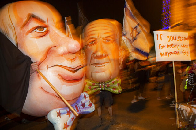 """FILE - In this Saturday, Aug. 8, 2020 file photo, demonstrators wear mask depicting Israel's Prime Minister Benjamin Netanyahu, left, and Defense Minister and coalition partner Benny Gantz, right, during a protest in Jerusalem, Israel. When  Netanyahu and his rival, Gantz, agreed to form an """"emergency"""" government in May after three bitter, and ultimately deadlocked, election campaigns, the goal was to stabilize Israeli politics in the face of a global pandemic. Less than 100 days later their fractious coalition government appears to be headed toward collapse as Israel grapples with a raging coronavirus outbreak, an economic calamity and a wave of public protests. (AP Photo/Ariel Schalit, File)"""