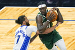 Milwaukee Bucks guard Jrue Holiday, right, tries to get by Orlando Magic guard Michael Carter-Williams (7) on his way to the basket during the first half of an NBA basketball game, Sunday, April 11, 2021, in Orlando, Fla. (AP Photo/John Raoux)