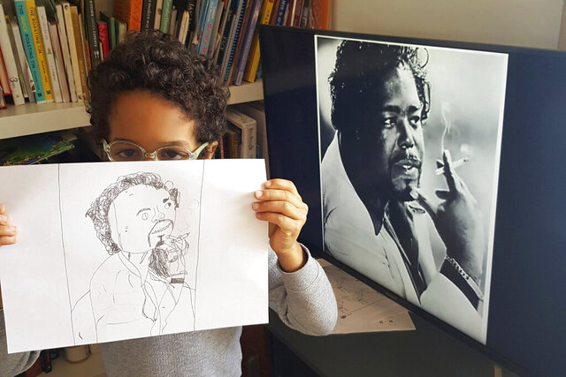 In this April 30, 2020, photo, Thomas, 6, holds up his drawing of American musician and producer Barry White that he sketched during the coronavirus pandemic while on lockdown in London. (AP Photo/Joana Mateus)
