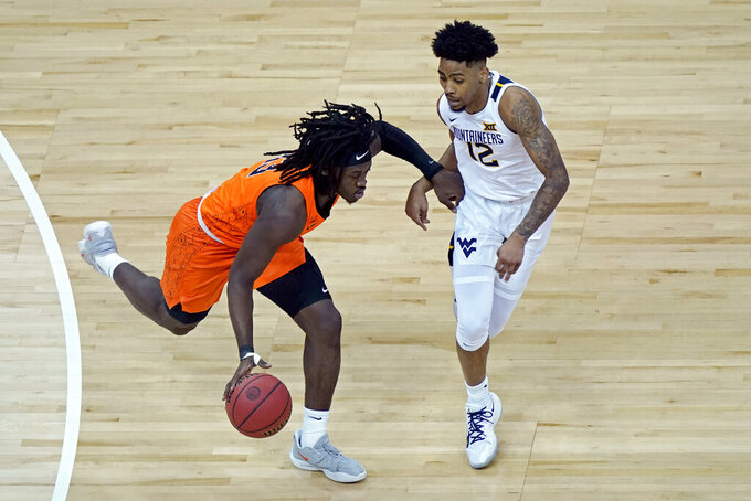 Oklahoma State's Isaac Likekele (13) drives past West Virginia's Taz Sherman (12) during the first half of an NCAA college basketball game in the second round of the Big 12 Conference tournament in Kansas City, Mo., Thursday, March 11, 2021. (AP Photo/Charlie Riedel)