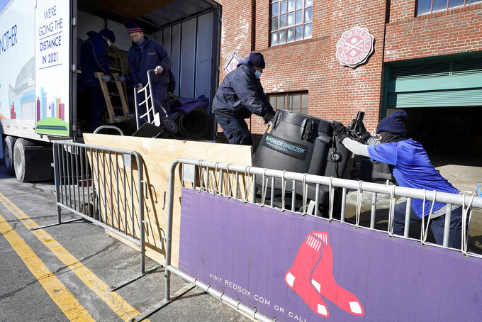 Workers load equipment onto the Boston Red Sox baseball team's truck outside Fenway Park, Monday, Feb. 8, 2021, in Boston. The truck is headed to JetBlue Park, in Fort Myers, Fla. for the players' spring training. (AP Photo/Steven Senne)