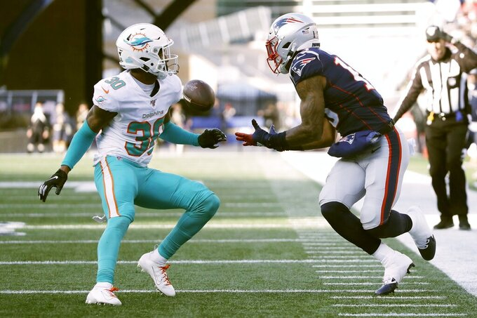 New England Patriots wide receiver N'Keal Harry, right, catches a pass along the sideline as Miami Dolphins defensive back Nate Brooks defends in the first half of an NFL football game, Sunday, Dec. 29, 2019, in Foxborough, Mass. (AP Photo/Elise Amendola)