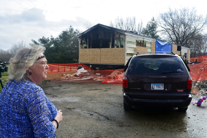 FILE - In this Sunday, April 7, 2019, file photo, Marie Chockley, a resident of the Timberline Trailer Court, north of Goodfield, Ill., surveys the damage that was caused by a Saturday night fire that killed five residents in a mobile home. A prosecutor says a central Illinois 9-year-old is expected to be charged Tuesday with five counts of first-degree murder in connection with the deadly mobile home fire. (Kevin Barlow/The Pantagraph via AP, File)