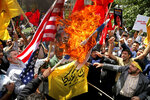 Demonstrators burn Israeli and U.S. flags to show their anger over the deaths of nearly 60 Palestinians along the Gaza border on Monday, during a protest inside the former U.S. embassy in Tehran, Iran, Wednesday, May 16, 2018. State media reported that Iran's President Hassan Rouhani has condemned the killing of Palestinians by Israel, saying