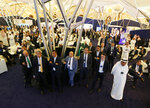Participants at the Future Investment Initiative forum watch a live screen during the opening session in Riyadh, Saudi Arabia, Tuesday, Oct. 29, 2019. The long-planned initial public offering of a sliver of Saudi Arabia's state-run oil giant Saudi Aramco will see shares traded on Riyadh's stock exchange in December, a Saudi-owned satellite news channel reported Tuesday as the kingdom's marquee investment forum got underway. (AP Photo/Amr Nabil)