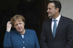 Irish Prime Minister Leo Varadkar looks at German Chancellor Angela Merkel as they pose at the entrance Farmleigh House for the media in Dublin, Ireland, Thursday, April 4, 2019. (AP Photo/Peter Morrison)