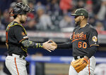 Baltimore Orioles relief pitcher Mychal Givens, right, and catcher Austin Wynns celebrate after they defeated the Cleveland Indians in a baseball game, Friday, May 17, 2019, in Cleveland. (AP Photo/Tony Dejak)