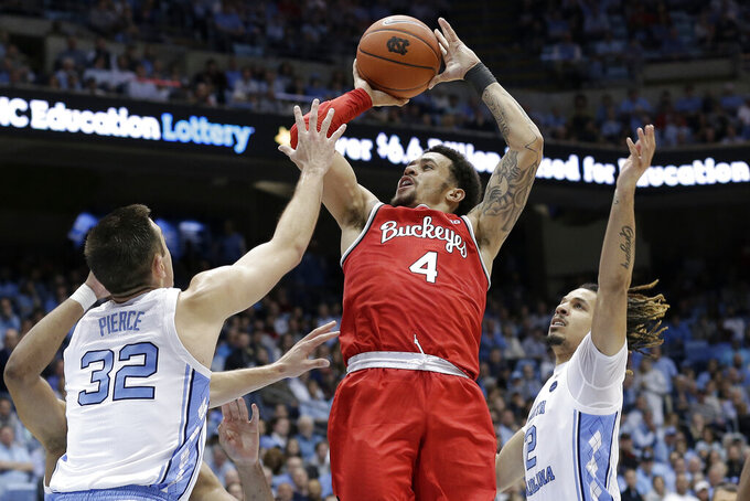 Ohio State guard Duane Washington Jr. (4) shoots while North Carolina guard Justin Pierce (32) and guard Cole Anthony (2) defend during the second half of an NCAA college basketball game in Chapel Hill, N.C., Wednesday, Dec. 4, 2019. Ohio State won 74-49. (AP Photo/Gerry Broome)