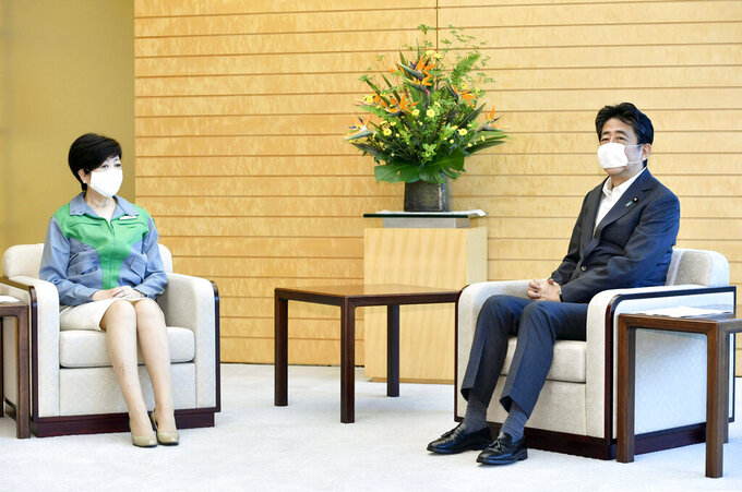 Tokyo Gov. Yuriko Koike, left, talks with Japanese Prime Minister Shinzo Abe at the prime minister's office in Tokyo Monday, July 6, 2020. Gov. Koike, who won her second term to head the Japanese capital in Sunday's election, met with her political rival, Prime Minister Abe and agreed to cooperate in their effort to fight against the coronavirus and to safely achieve the Olympics next year. (Yoshitaka Sugawara/Kyodo News via AP)