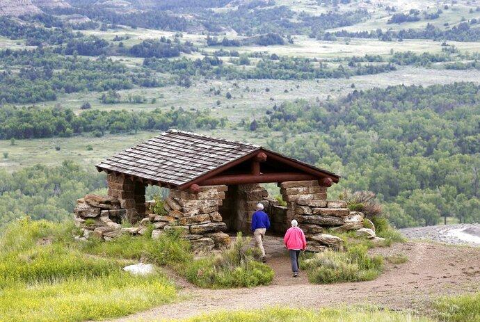 FILE - In this June 11, 2014, file photo, visitors hike to a stone lookout over the Little Missouri River inside the Theodore Roosevelt National Park, located in the Badlands of North Dakota. Meridian Energy Group CEO William Prentice told The Associated Press last Friday, Aug. 16, 2019, that the company hopes to have a $800 million oil refinery operating in 2022, just 3 miles from the park. Prentice added lawsuits have made investors skittish and delayed progress on the refinery. (AP Photo/Charles Rex Arbogast, File)