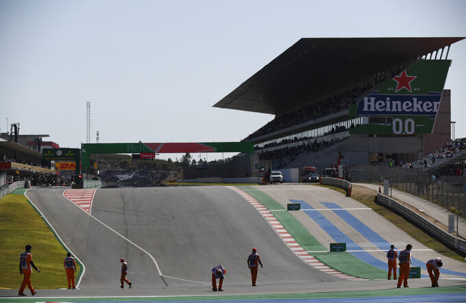 Track workers check the track prior to the qualification session for the Formula One Portuguese Grand Prix at the Algarve International Circuit in Portimao, Portugal, Saturday, Oct. 24, 2020. The Formula One Portuguese Grand Prix will take place on Sunday. (Jorge Guerrero, Pool via AP)