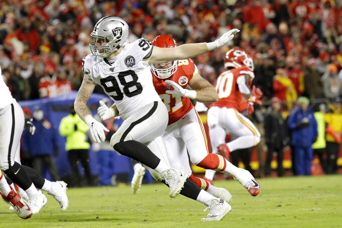 FILE - In this Dec. 1, 2019, file photo, Oakland Raiders defensive end Maxx Crosby (98) gets past Kansas City Chiefs tight end Blake Bell (81) during the second half of an NFL football game in Kansas City, Mo. Thanks to having three first-round picks last year because of trades that sent established stars Khalil Mack and Amari Cooper away, the Raiders have gotten more touchdowns (14), sacks (11), yards rushing (1,079) and receptions (82) than any other class of rookies this season thanks in large part to strong performances from first-round running back Josh Jacobs and fourth-round defensive end Maxx Crosby. (AP Photo/Charlie Riedel, File)