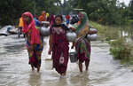 Indian women carrying drinking water walk through a flooded road in Burha Burhi village, east of Gauhati, Assam, India, Monday, July 15, 2019. After causing flooding and landslides in Nepal, three rivers are overflowing in northeastern India and submerging parts of the region, affecting the lives of more than 2 million, officials said Monday. (AP Photo/Anupam Nath)