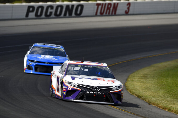 Denny Hamlin (11) drives through Turn 3 during a NASCAR Cup Series auto race, Sunday, July 28, 2019, in Long Pond, Pa. Hamlin won the race. (AP Photo/Derik Hamilton)