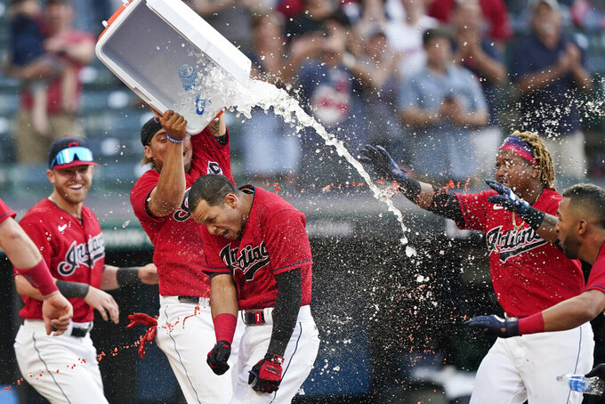Cleveland Indians teammates douse Cesar Hernandez, center, after he hit the winning two-run home run in the 10th inning of a baseball game against the Minnesota Twins, Saturday, May 22, 2021, in Cleveland. (AP Photo/Tony Dejak)