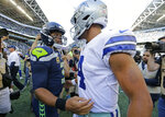 FILE - In this Sept. 23, 2018, file photo, Seattle Seahawks quarterback Russell Wilson, left, greets Dallas Cowboys quarterback Dak Prescott, right, following an NFL football game in Seattle. Russell Wilson won a playoff game with Seattle as a rookie, a Super Bowl in his second season and another NFC championship the third time around. The best Dak Prescott can hope for with the Dallas Cowboys is to join Wilson on that list of Super Bowl winners in his third year, a quest that will start with the first postseason meeting of quarterbacks with quite a bit in common, other than postseason pedigree.(AP Photo/John Froschauer, File)