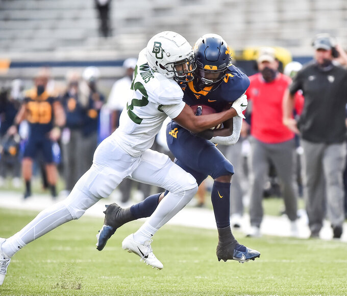 West Virginia running back Leddie Brown (4) is tackled by Baylor safety JT Woods (22) during an NCAA college football game, Saturday, Oct. 3, 2020, in Morgantown, W.Va. (William Wotring/The Dominion-Post via AP)