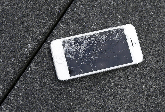 FILE - This Aug. 26, 2015 photo shows an Apple iPhone with a cracked screen after a drop test from the DropBot, a robot used to measure the sustainability of a phone to dropping, at the offices of SquareTrade in San Francisco.   As  software and technology gets infused in more and more products, manufacturers are increasingly making those products difficult to repair, potentially costing business owners time and money. Makers of products ranging from smartphones to farm equipment can withhold repair tools and create software-based locks that prevent even simple updates, unless they're done by a repair shop authorized by the company.  (AP Photo/Ben Margot, File)