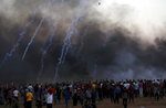 Protesters gather while Israeli troops fired teargas near the fence of Gaza Strip border with Israel during a protest east of Gaza City, Friday, Sept. 14, 2018. Gaza health officials say 3 Palestinians, including 12-year-old boy, were killed by Israeli army fire in protests along Gaza's perimeter fence. (AP Photo/Adel Hana)