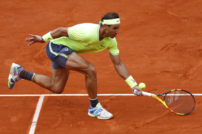 FILE - In this June 9, 2019, file photo, Spain's Rafael Nadal reaches for the ball as he plays Austria's Dominic Thiem during the men's final of the French Open tennis tournament at Roland Garros stadium in Paris. If the French Open were being held as scheduled right now, Nadal would have been seeking a 20th Grand Slam title to equal Roger Federer's record for men. (AP Photo/Jean-Francois Badias, File)
