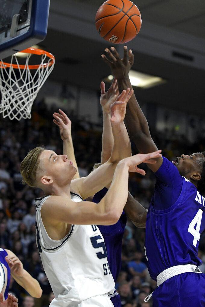 Utah State center Kuba Karwowski (52) and Weber State guard Kham Davis (4) reach for a rebound during the first half of an NCAA college basketball game Friday, Nov. 8, 2019, in Logan, Utah. (AP Photo/Eli Lucero)