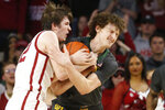 Oklahoma guard Austin Reaves, left, and Baylor guard Matthew Mayer fight for control of the ball during the first half of an NCAA college basketball game in Norman, Okla., Tuesday, Feb. 18, 2020. (AP Photo/Sue Ogrocki)