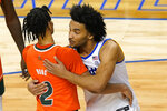 Miami (Fl) guard Isaiah Wong (2) gets a hug from Pittsburgh forward Justin Champagnie, right, after their NCAA college basketball game in the first round of the Atlantic Coast Conference tournament in Greensboro, N.C., Tuesday, March 9, 2021. Miami won the game 79-73. (AP Photo/Gerry Broome)