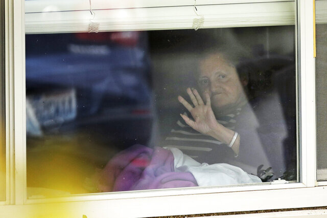 Susan Hailey, who has tested positive for the new coronavirus, waves through the window of her room at the Life Care Center in Kirkland, Wash., as her daughter leaves after a visit, Tuesday, March 17, 2020, near Seattle. In-person visits are not allowed at the nursing home, which has been at the center of the outbreak of new coronavirus in the state. (AP Photo/Ted S. Warren)