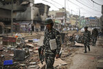 Indian paramilitary soldiers patrol a street vandalized in Tuesday's violence in New Delhi, India, Thursday, Feb. 27, 2020. India accused a U.S. government commission of politicizing communal violence in New Delhi that killed at least 30 people and injured more than 200 as President Donald Trump was visiting the country. The violent clashes between Hindu and Muslim mobs were the capital's worst communal riots in decades and saw shops, Muslim shrines and public vehicles go up in flames. (AP Photo/Altaf Qadri)