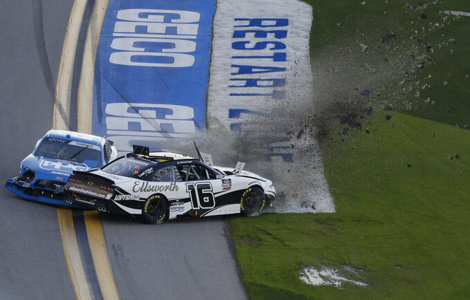 A J Allmendinger (16) and Austin Cindric (22) crash during the NASCAR Xfinity Series road course auto race at Daytona International Speedway, Saturday, Feb. 20, 2021, in Daytona Beach, Fla. Allmendinger was leading the race at the time. (AP Photo/Terry Renna)