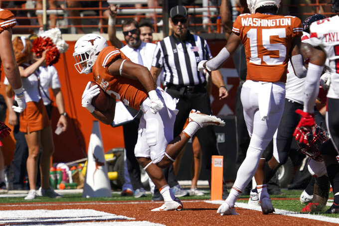 Texas running back Roschon Johnson (2) runs for a touchdown against Texas Tech during the first half of an NCAA college football game on Saturday, Sept. 25, 2021, in Austin, Texas. (AP Photo/Chuck Burton)