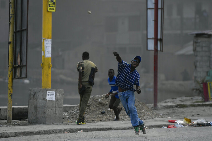 A protester demanding justice for the assassinated President Jovenel Moise hurls a stone in Cap-Haitien, Haiti, Thursday, July 22, 2021. Demonstrations after a memorial service for Moise turned violent on Thursday afternoon with protesters shooting into the air, throwing rocks and overturning heavy concrete barricades next to the seashore as businesses closed and people took cover. (AP Photo/Matias Delacroix)