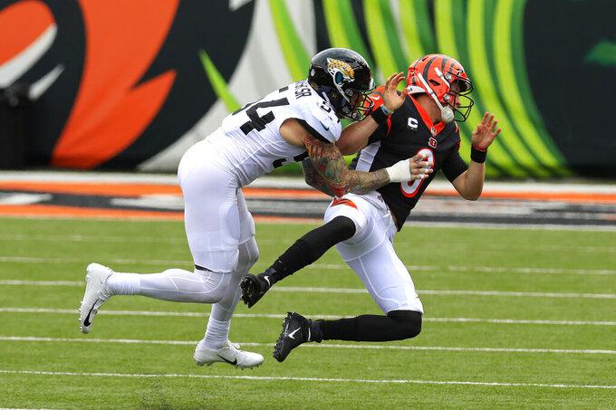 Cincinnati Bengals quarterback Joe Burrow (9) is hit by Jacksonville Jaguars defensive end Cassius Marsh (54) after a throw in the first half of an NFL football game in Cincinnati, Sunday, Oct. 4, 2020. (AP Photo/Aaron Doster)
