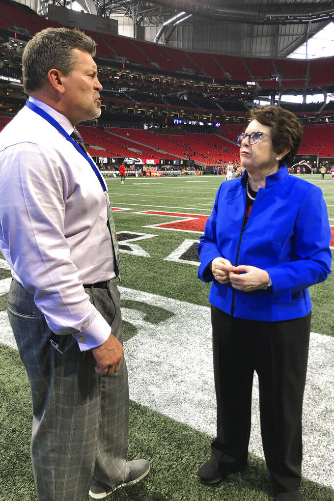 Former NFL player and ESPN broadcaster Mark Schlereth, left, speaks with former number one women's tennis player Billie Jean King before an NFL football game between the Atlanta Falcons and the Tampa Bay Buccaneers, Sunday, Nov. 24, 2019, in Atlanta. (AP Photo/Mike Stewart)