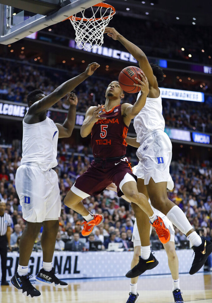 Virginia Tech guard Justin Robinson (5) drives to the basket between Duke forward Zion Williamson (1) and center Marques Bolden during the second half of an NCAA men's college basketball tournament East Region semifinal in Washington, Friday, March 29, 2019. (AP Photo/Patrick Semansky)
