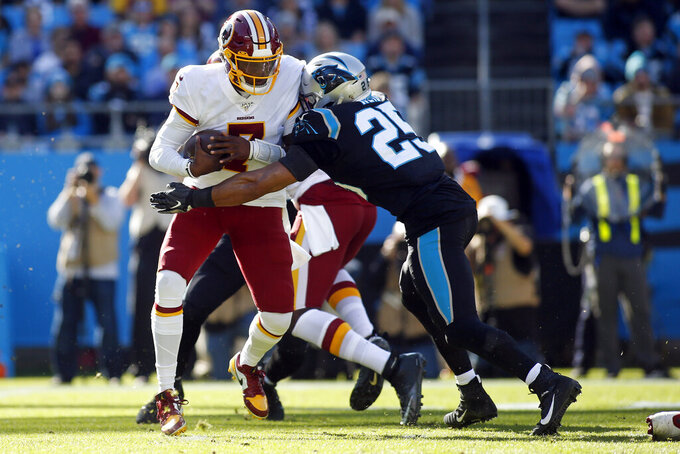 Carolina Panthers strong safety Eric Reid (25) rushes Washington Redskins quarterback Dwayne Haskins (7) during the first half of an NFL football game in Charlotte, N.C., Sunday, Dec. 1, 2019. (AP Photo/Brian Blanco)