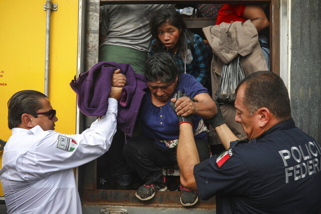 In this Nov. 26, 2019 photo, a federal police officer assigned to the National Guard and a migration agent help a woman off the cargo hold of a truck packed with migrants being smuggled, at an immigration checkpoint where the truck was stopped in Medellín de Bravo, Veracruz state, Mexico. The final tally of people being smuggled in the truck was 74. (AP Photo/Felix Marquez)