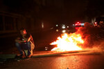 A protester sits next to burning tires, as he blocks a main street by burning tires, after a top court suspended a Central Bank decree that allowed the Lebanese to withdraw from dollar deposits at a rate two and a half times better than the fixed exchange rate, in downtown Beirut, Lebanon, early Thursday, June 3, 2021. In a late night burst of anger, dozens of protesters blocked main roads in Beirut and north of the capital to protest against the constant humiliation of Lebanese who line up to fill their cars with fuel, increasing power cuts, search for medicine and deal with confused banking decisions that are robbing thousands of their savings. (AP Photo/Hussein Malla)
