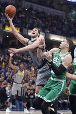 Indiana Pacers forward Bojan Bogdanovic (44) shoots over Boston Celtics forward Jayson Tatum (0) during the first half of an NBA basketball game in Indianapolis, Friday, April 5, 2019. (AP Photo/Michael Conroy)