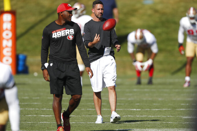 San Francisco 49ers head coach Kyle Shanahan, back, tosses a ball as defensive backs coach Joe Woods looks on during a combined NFL training camp with the Denver Broncos Saturday, Aug. 17, 2019, at the Broncos' headquarters in Englewood, Colo. (AP Photo/David Zalubowski)