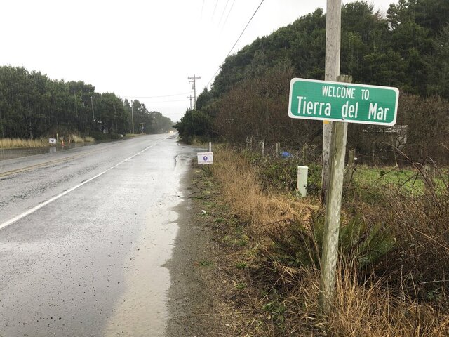 A sign welcomes motorists to Tierra del Mar, Ore., Wednesday, Jan. 8, 2020. The tiny coastal village is opposing a plan by Facebook to build a landing spot for a submarine cable connecting America with Asia. (AP Photo/Andrew Selsky)