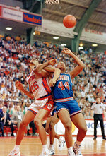 FILE - In this March 14, 1991, file photo, Syracuse's LeRon Ellis (25) and Richmond's Kenny Wood (44) lock arms as they watch the ball get away during the first half and an NCAA college basketball East Regional game in College Park, Md. Richmond defeated Syracuse 73-69. (AP Photo/Doug Mills, File)