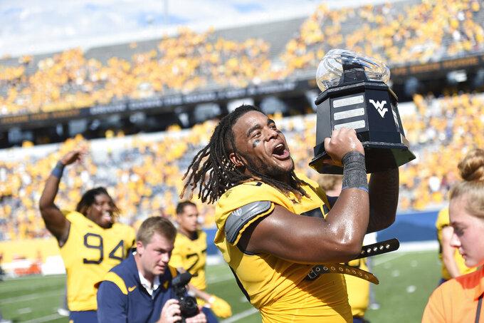 West Virginia defensive lineman Dante Stills (55) hoist the Black Diamond Trophy after defeating Virginia Tech in an NCAA college football game in Morgantown, W.Va., Saturday, Sep. 18, 2021. (AP Photo/William Wotring)