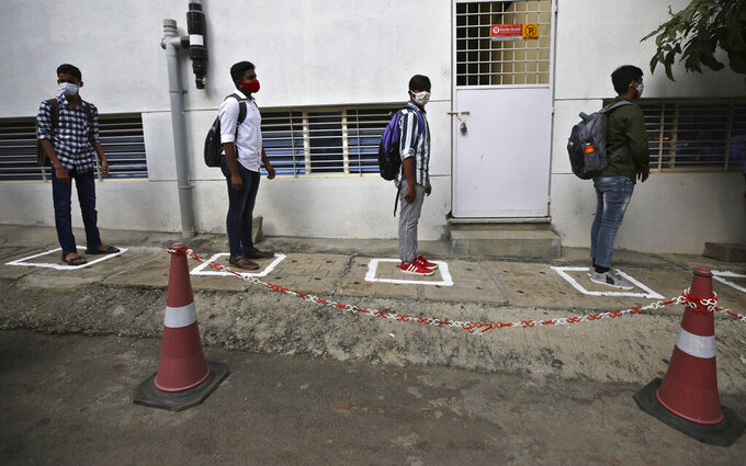 Students wearing face masks and maintain social distancing as a precaution against the coronavirus wait to enter the school in Bengaluru, India, Friday, Jan. 1, 2021. The southern state of Karnataka on Friday opened schools for students of grade 10 and 12 after a gap of more than nine months. India has more than 10 million cases of coronavirus, second behind the United States. (AP Photo/Aijaz Rahi)