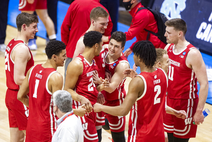 Wisconsin players celebrate after defeating North Carolina in a first-round game in the NCAA men's college basketball tournament, Friday, March 19, 2021, at Mackey Arena in West Lafayette, Ind. (AP Photo/Robert Franklin)