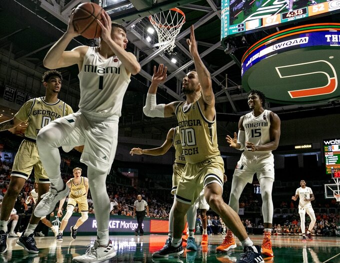 Miami guard Dejan Vasiljevic (1) looks to pass to center Ebuka Izundu (15) as Georgia Tech guard Jose Alvarado (10) defends in the second half of an NCAA college basketball game in Coral Gables, Fla., on Saturday, Feb. 23, 2019. (Al Diaz/Miami Herald via AP)