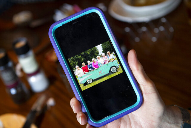 In this Wednesday, Jan. 8, 2020, photo, Sandy Brisson, of Millersville, holds out her phone to show a photo of the tight-knit group of friends on one of their many excursions over the past 60 years, in Lancaster, Pa. Over the past 60 years, women have left the group and others have joined, but this core lunch bunch of eight retirees still meets at a different restaurant every second Wednesday of the month. (Ty Lohr/LNP/LancasterOnline via AP)