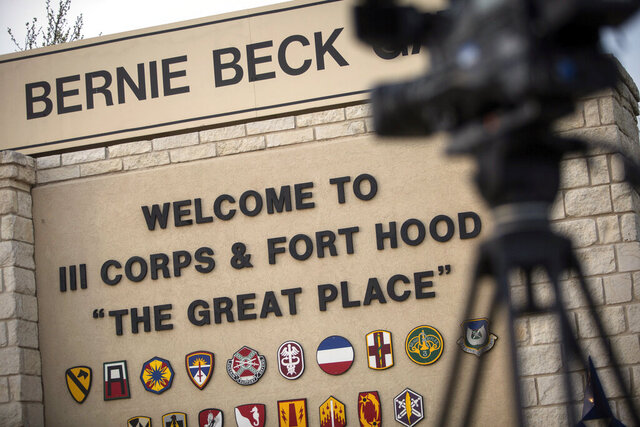 FILE - In this April 2, 2014, file photo, members of the media wait outside of the Bernie Beck Gate, an entrance to the Fort Hood military base in Fort Hood, Texas. Federal agents have seized more than 20 vehicles and the money in 10 bank accounts from a couple of U.S. Army veterans in Texas, who they say used personal information stolen from soldiers to defraud the military out of as much as $11 million. In an affidavit filed in court in June 2020 seeking to search the couple's home in Killeen, near Fort Hood, investigators described how they allegedly used a transportation reimbursement program to swindle the Army out of $2.3 million to $11.3 million. (AP Photo/Tamir Kalifa, File)